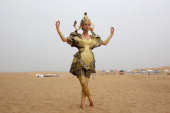 A model in Mongolia costumes poses for photos in Xiangshawan Desert also called Sounding Sand Desert on July 21 2013 in Ordos of Inner Mongolia...