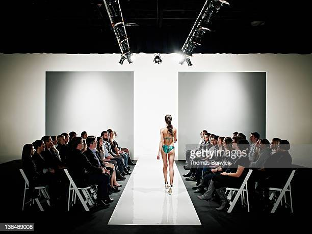 Model in swimsuit walking down catwalk