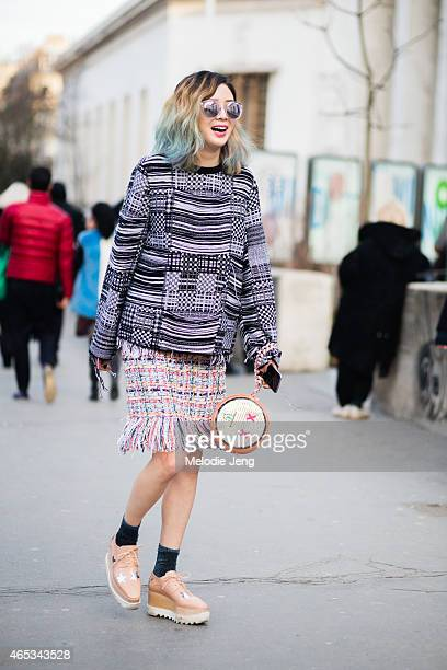 Model Irene Kim wears a Hoeohwan Smulation top Chanel skirt am Irene x Play No More bag and Stella McCartney creepers on March 5 2015 in Paris France