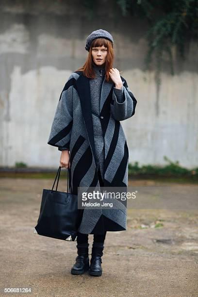 Model Irina Kravchenko wears a Ukrainian designer LITKOVSKAYA oversized gray coat with black stripes and a gray beret on January 24 2016 in Paris...