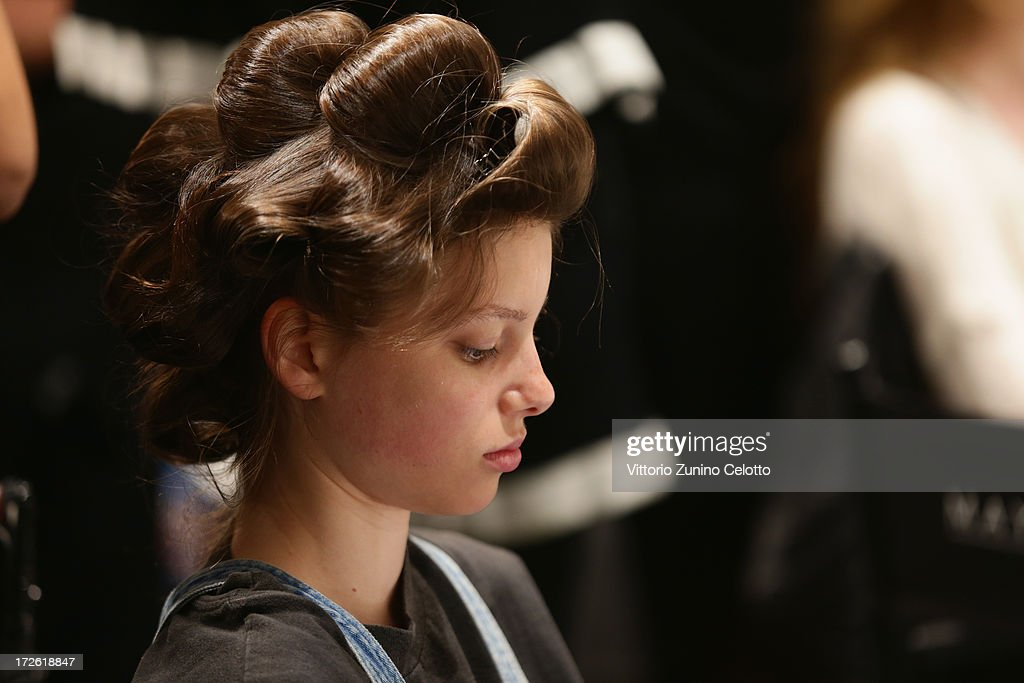 A model is gettting styled backstage ahead of the Dietrich Emter Show during the Mercedes-Benz Fashion Week Spring/Summer 2014 at Brandenburg Gate on July 4, 2013 in Berlin, Germany
