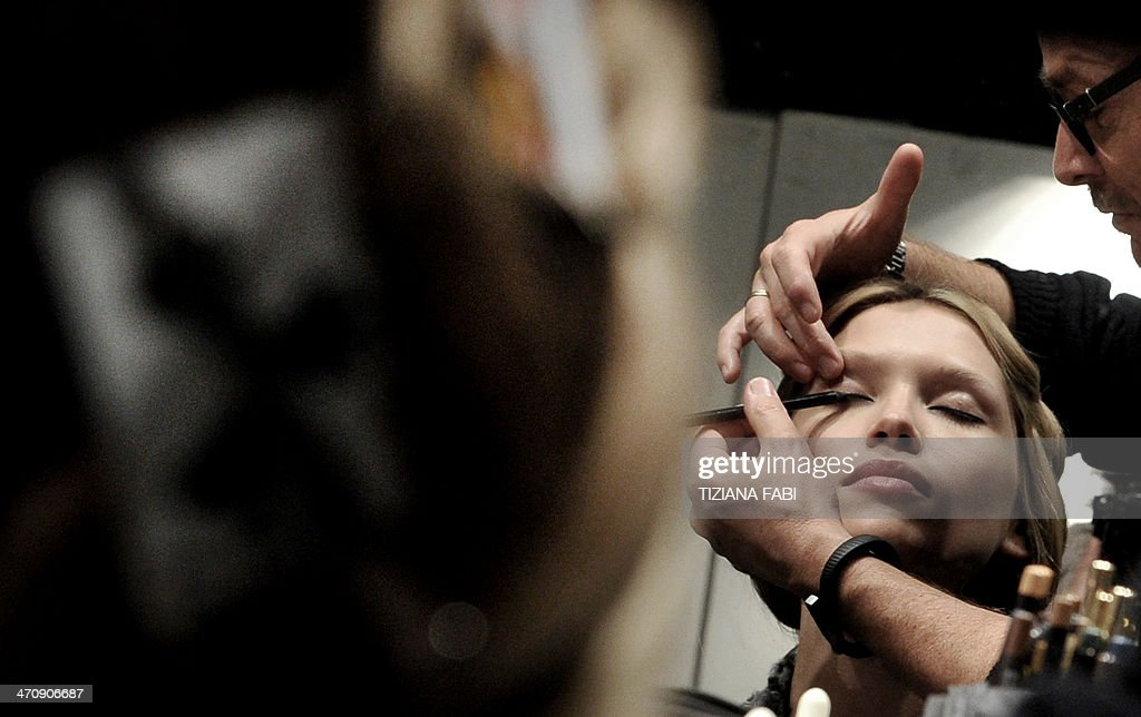 A model is pictured backstage as a make-up artist prepares her for the Blumarine show during Milan's Women's fashion week Autumn/Winter 2014 collections on February 21, 2014. AFP PHOTO / TIZIANA FABI