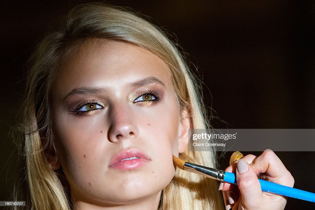 A model is prepared backstage at the Kristian Aadnevik show during London Fashion Week SS14 at The Royal Horseguards on September 15, 2013 in London, England. The model wears Frontcover Cosmetics.