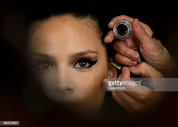A model is prepared by makeup artist prior to presenting a creation of Andres Sarda SpringSummer 2014 collection during the Madrid Fashion Week in...