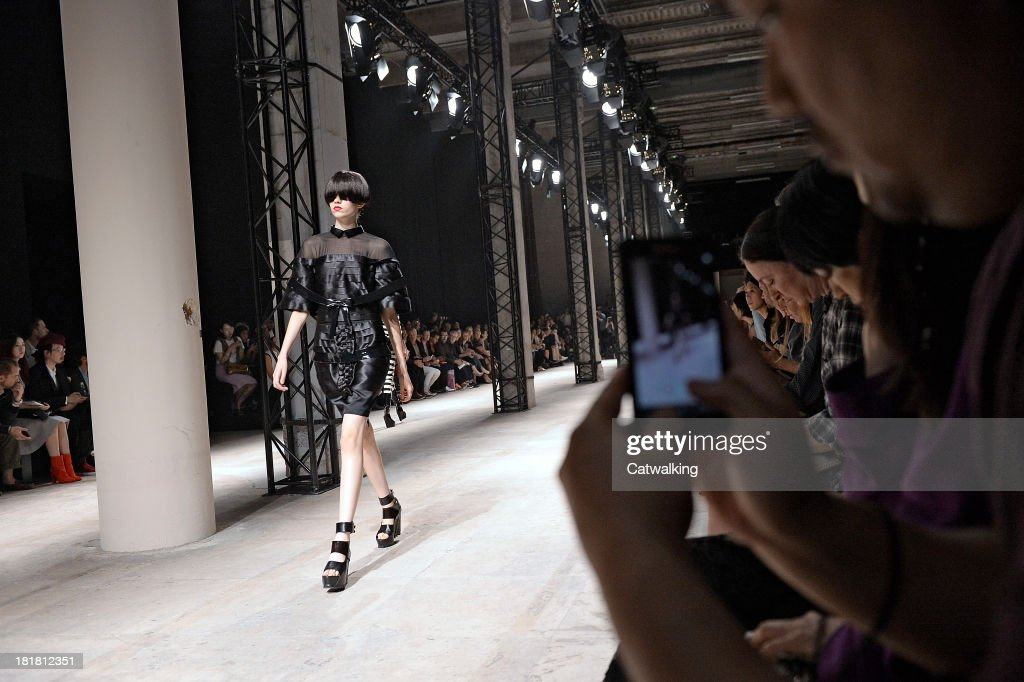A model is recorded on smart phones and iPhones as she walks the runway at the Undercover Spring Summer 2014 fashion show during Paris Fashion Week on September 25, 2013 in Paris, France.