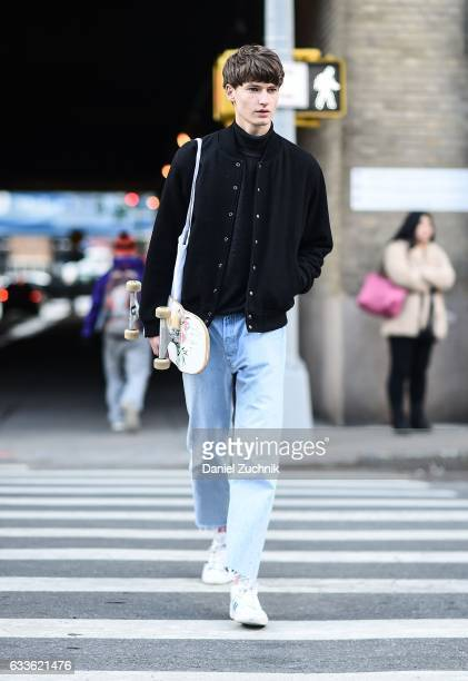 A model is seen wearing a black jacket blue jeans with a skateboard outside of the STAMPD show during New York Fashion Week Men's AW17 on February 2...