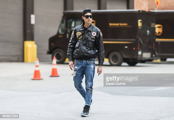 A model is seen wearing a black patched leather jacket and blue jeans outside of the General Idea show during New York Fashion Week Men's AW17 on...