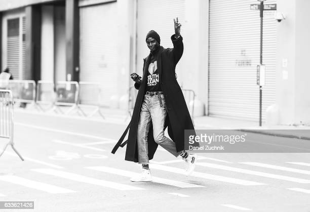 A model is seen wearing a blue coat South Sudan shirt blue jeans and Comme Des Garcons sneakers outside of the STAMPD show during New York Fashion...