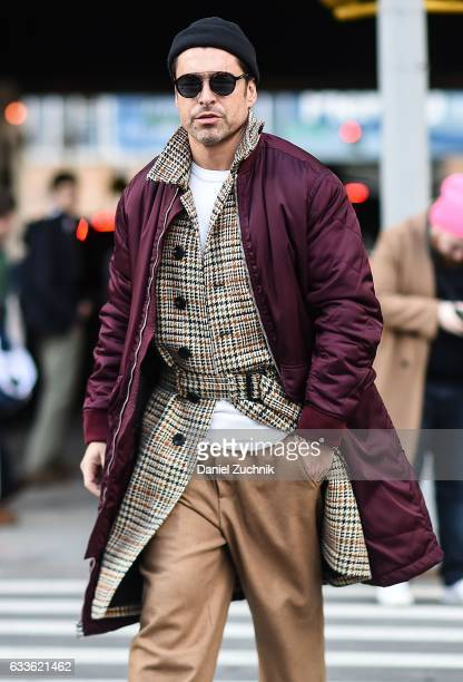 A model is seen wearing a burgundy coat plaid inner coat and brown pants outside of the STAMPD show during New York Fashion Week Men's AW17 on...