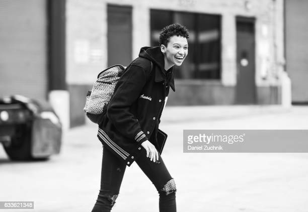 A model is seen wearing a varsity jacket black jeans and checkered backpack outside of the STAMPD show during New York Fashion Week Men's AW17 on...