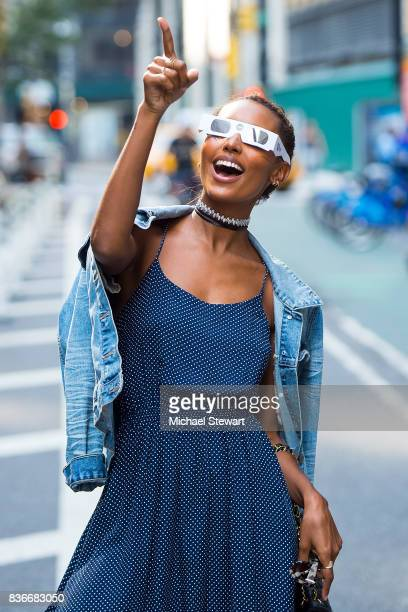 Model Jasmine Tookes views the solar eclipse using solar glasses in Midtown on August 21 2017 in New York New York