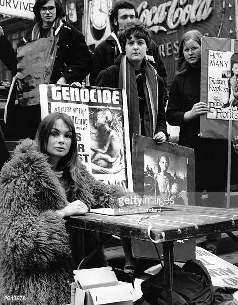Model Jean Shrimpton signs a book of protest against British complicity in the NigeriaBiafran War during a 48hour fast in Piccadilly Circus London
