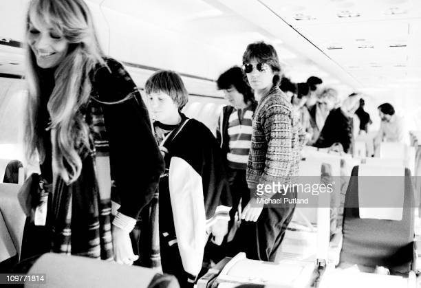 Model Jerry Hall on a plane from Scotland with singer Mick Jagger and bassist Bill Wyman of the Rolling Stones during their 1982 European Tour
