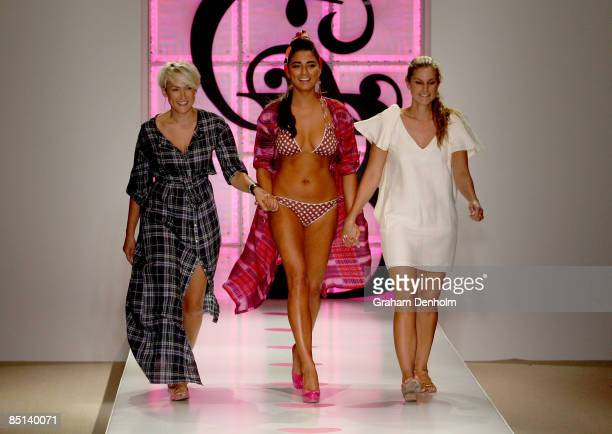 Model Jessica Gomes showcases a design on the catwalk by Anna Boy alongside label designers Anna Hewett and Lill Boyd during day three of Swim...