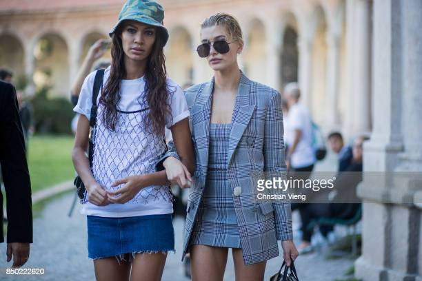 Model Joan Smalls wearing a camouflage hat white tshirt denim skirt and model Hailey Baldwin wearing a grey checked dress grey checked blazer jacket...