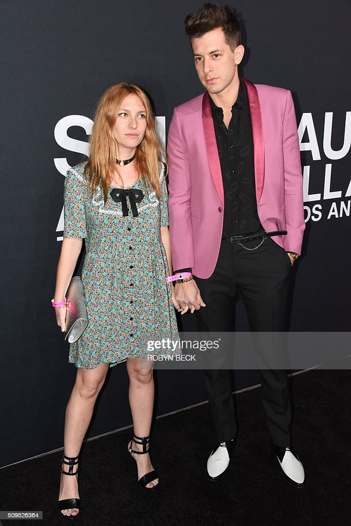 Model Josephine de La Baume and recording artist Mark Ronson (R) attend the Saint Laurent men's fall line and the first part of its women's collection fashion show at the Paladium, in Hollywood, California, February 10, 2016. / AFP / ROBYN BECK