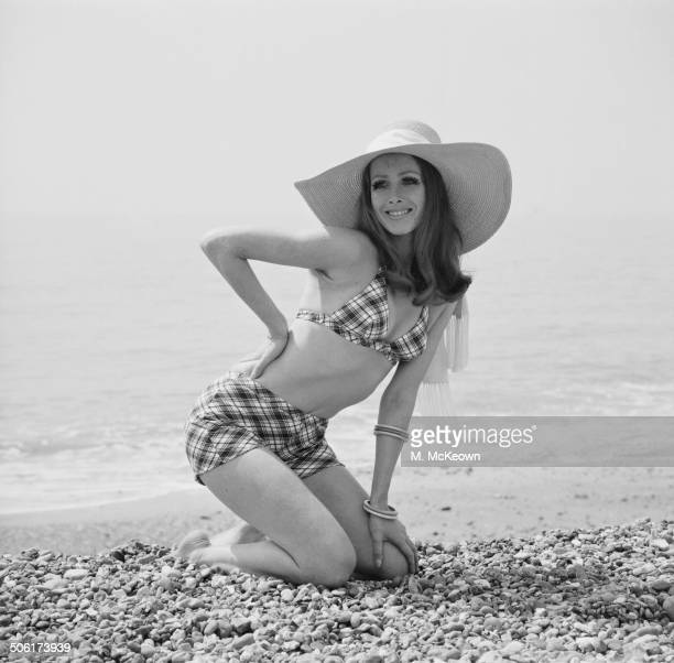 Model Justine poses on the beach wearing a Helanca bikini 1969