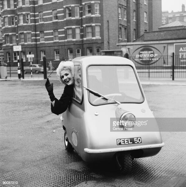 Model Karen Burch at the wheel of a Peel P50 a new microcar produced by the Manx Peel Engineering Company outside the Earl's Court Exhibition Centre...
