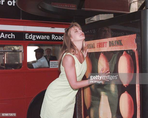 Model Karen Hill takes in the aroma of Del Monte's new fruit drink Batik at a bus stop in the centre of London today as the new concept poster...