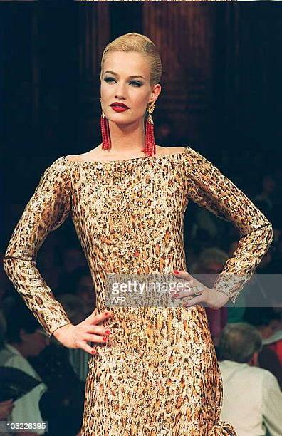 Model Karen Mulder presents a panther pelt in gold on a long lame sheath for evenings during Yves SaintLaurent FallWinter 19951996 highfashion...