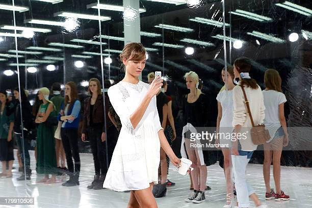 Model Karlie Kloss on her iphone during the runthrough of the Prabal Gurung show during Spring 2014 MercedesBenz Fashion Week at Skylight at Moynihan...