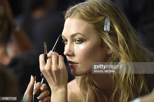 US model Karlie Kloss receives makeup on backstage before the Italian fashion designer Donatella Versace Haute Couture FallWinter 2015/2016...