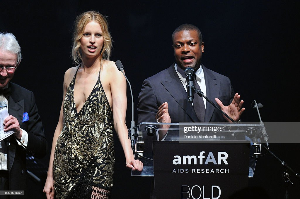 Model Karolina Kurkova (L) and actor Chris Tucker speak during amfAR's Cinema Against AIDS 2010 benefit gala at the Hotel du Cap on May 20, 2010 in Antibes, France.
