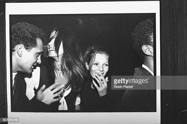 Model Kate Moss smoking at her 19th bday party w model Elle MacPhearson in between two unident men