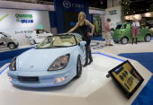 Model Kelly McManus of Grosse Pointe Woods Michigan poses with ther CTT C2 C Square electric vehicle displayed during the press preview for the world...