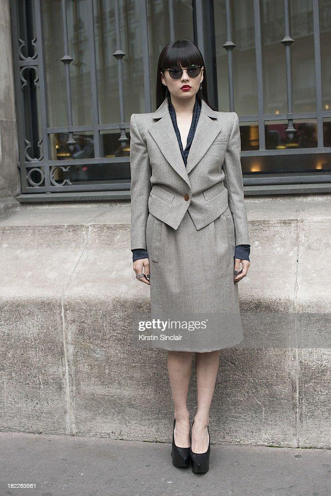 Model Kozue Akimoto wears a Vivienne Westwood suit, sunglasses and shoes on day 5 of Paris Fashion Week Spring/Summer 2014, Paris September 28, 2013 in Paris, France.