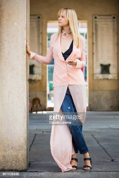 Model Kris Agapova wears a La Perla pink jacket Ynot jeans Asos black shoes and Solipsi pink leather choker on June 26 2017 in Milan Italy