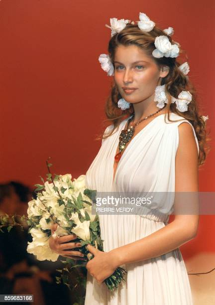 Model Laetitia Casta wears the a long pleaded decollete sleeveless wedding dress by Yves Saint Laurent for his Spring/Summer '99 readytowear...