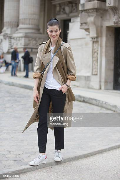 Model Larissa Hofmann wears a Burberry trenchcoat Miu Miu purse and Adidas Stan Smith sneakers after Chanel on Day 3 of Paris Haute Couture Fashion...