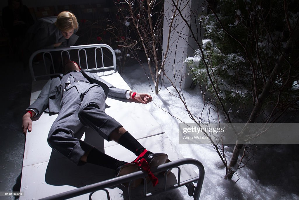 A model lies tied to a bed on the runway during the Thom Browne fall 2013 presentation during Mercedes-Benz Fashion Week at Center 548 on February 11, 2013 in New York City.