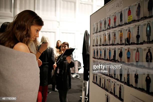 A model looks at a model board backstage ahead of the Laurel show during the MercedesBenz Fashion Week Berlin Autumn/Winter 2015/16 at Brandenburg...