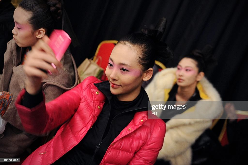 A model (C) looks at her cellphone backstage before the Minzu University of China Collection at China Fashion Week in Beijing on March 27, 2013. China Fashion Week runs from March 24 to March 30.