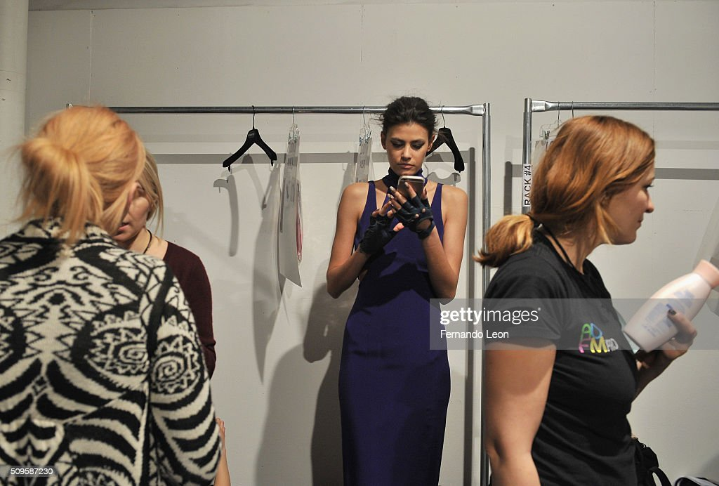 A model looks at her phone while preparations are made for The Jay Godfrey Fall 2016 presentation during New York Fashion Week: The Shows at The Space, Skylight at Clarkson Square on February 11, 2016 in New York City.