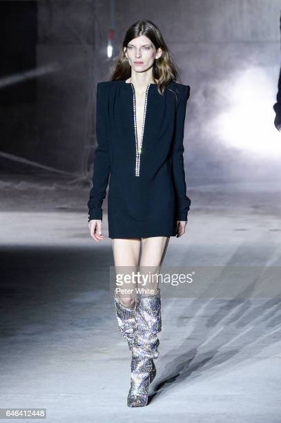 Model Luca Gadjus walks the runway during the Saint Laurent show as part of the Paris Fashion Week Womenswear Fall/Winter 2017/2018 on February 28...