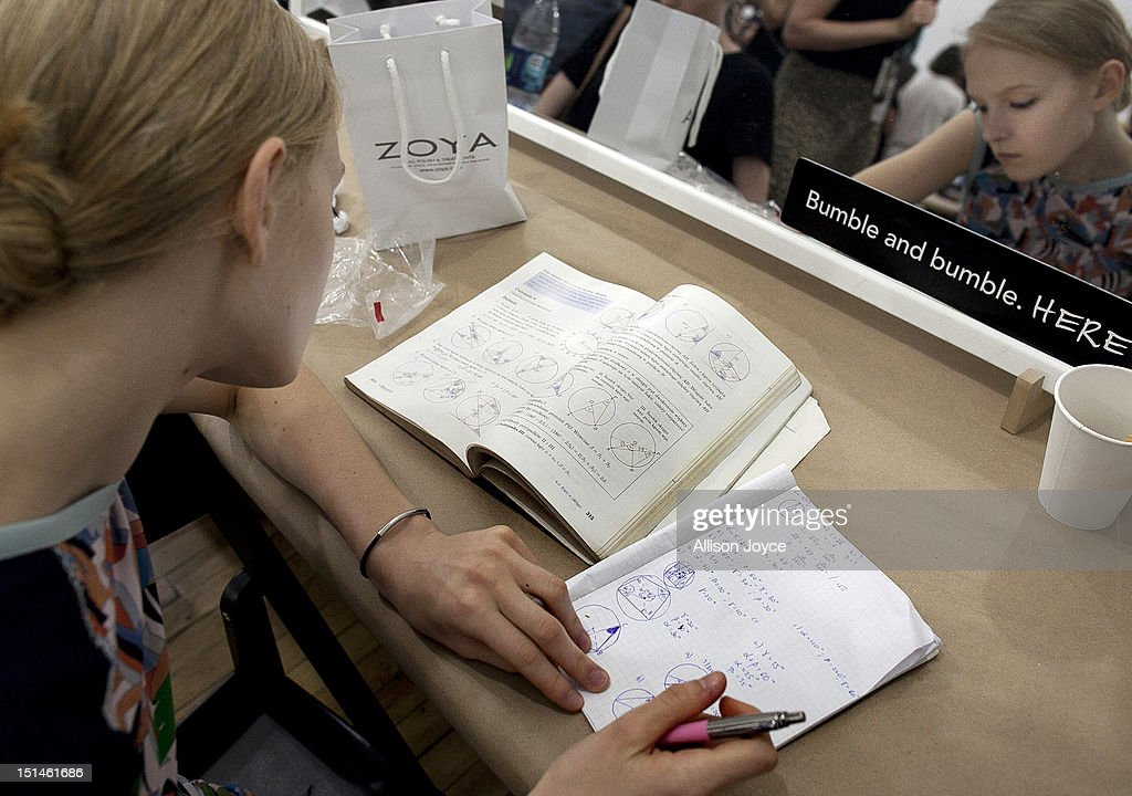 Model Maja does homework kackstage during the Yigal Azrouel spring 2013 fashion show during Mercedes-Benz Fashion Week at Highline Stages on September 7, 2012 in New York City.
