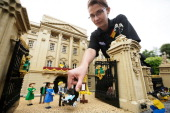 Model maker Katrina James places a Lego model of HRH Prince George of Cambridge outside a model of Buckingham Palace part of a new attraction created...