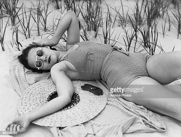 Model Marcella Flood relaxes in a onepiece swimsuit at Long Beach California June 1937