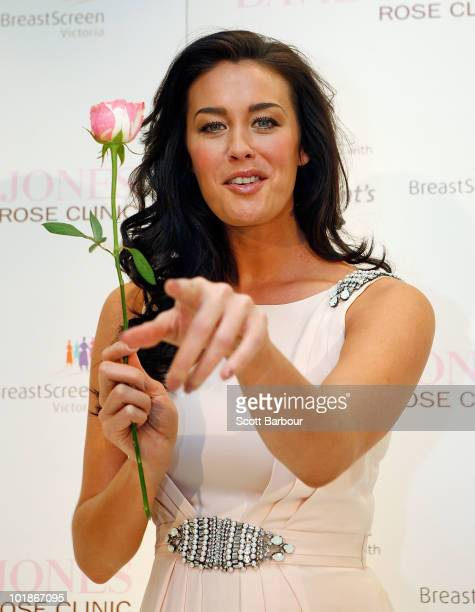 Model Megan Gale gestures while holding a rose during the announcement of a new women's health initiative at David Jones Bourke Street Mall on June 8...