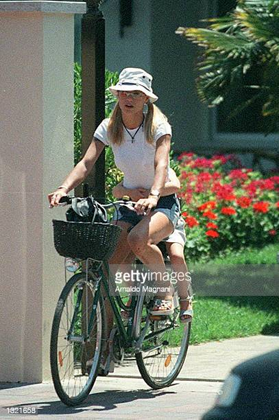Model Michelle Hunziker the wife of Italian pop star Eros Ramazzotti rides a bicycle with her daughter Aurora July 2 2001 in Milan