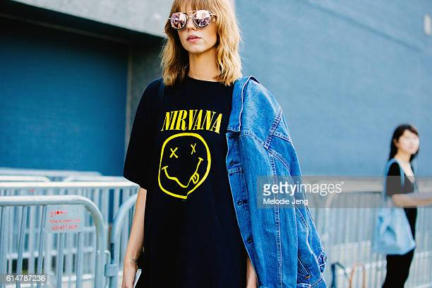 Model Michi Delane wears vintagestyle reflective sunglasses a black Nirvana tshirt and a denim jacket off her shoulder after the Lacoste show at...