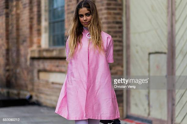 Model Mimie Lashiry wearing a pink House of Cards Double Box Pleat dress and white Mesh Catsuit outside Emma Mulholland at MercedesBenz Fashion Week...