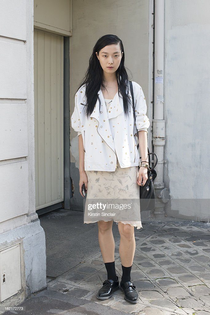 Model Model Sung Hee wears Doc Martins shoes, Prada bag and all else is vintage on day 4 of Paris Fashion Week Spring/Summer 2014, Paris September 27, 2013 in Paris, France.