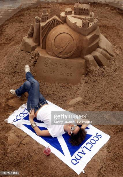 Model Monica Mira with a sand sculpture on Castle Street in Edinburgh it contains 100 flight tickets and depicts Gaudi cathedral and Edinburgh castle...