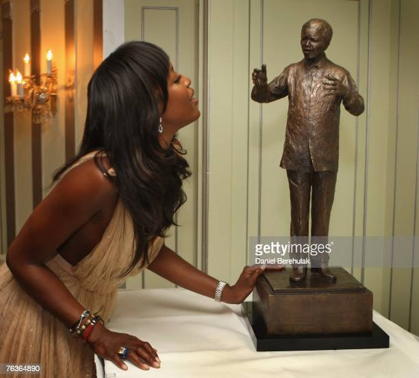 Model Naomi Campbell observes a statue of Nelson Mandella during an honourary dinner at the Dorchester Hotel on August 28 2007 in London England...