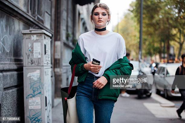 Model Nastya Abramova wears a green puffer jacket off her shoulders a white shirt blue jeans Celine bag and an accessory around her neck after the...