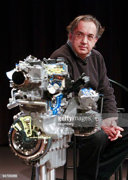 A model of a 14liter Fiat SpA fourcylinder engine sits on display foreground while Sergio Marchionne chief executive officer of Fiat and Chrysler...